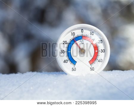Thermometer with celsius scale placed in a fresh snow showing sub-zero temperature minus 11 degree - cold winter weather concept