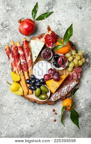 Appetizers Table With Antipasti Snacks. Cheese And Meat Variety Board Over Grey Concrete Background.