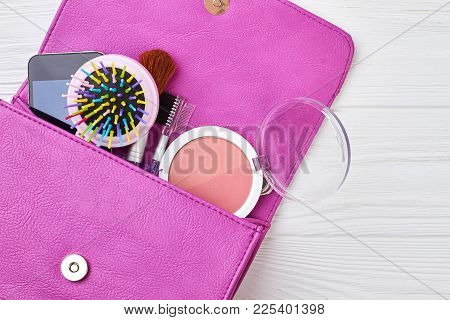 Women Bag And Lady Stuff. Contents Of Women Pink Bag On Wooden Background. Female Cosmetics And Acce