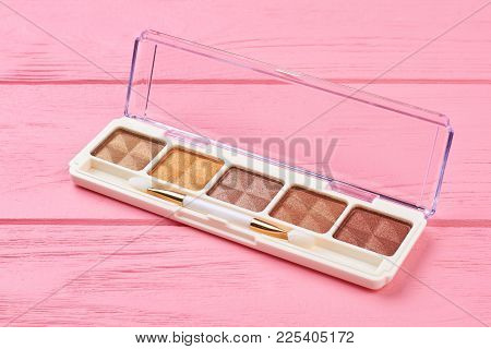 Set Of Brown Eyeshadows, Wooden Background. Beige And Nude Color Eyeshadows On Pink Background. Deco