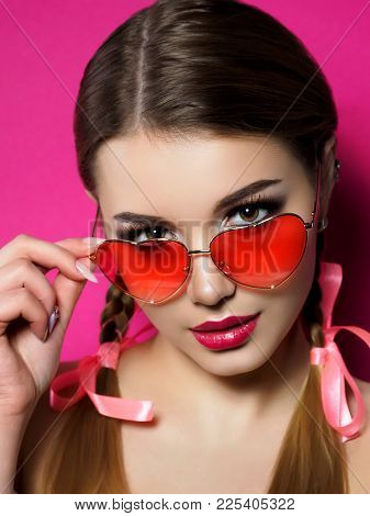 Young Beautiful Playful Woman Looks Over Her Heart Shaped Red Glasses. Valentines Day, Love Or Theme