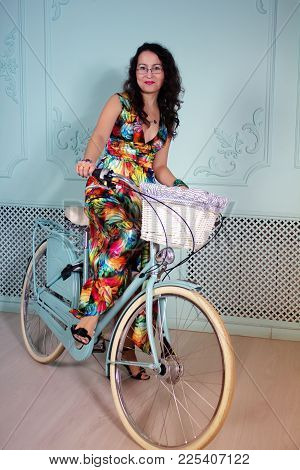 Studio Portrait Of A Beautiful Asian Woman In Colorful Dress With Bicycle
