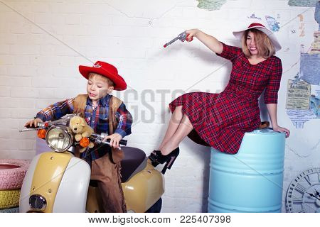 Mother And Son Having Fun. Studio Image With Scooter And Barrels As A Background
