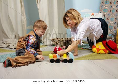Happy Mother And Son Playing With Colorful Toys Indoor. The Happy Family Spends Time Together At Hom