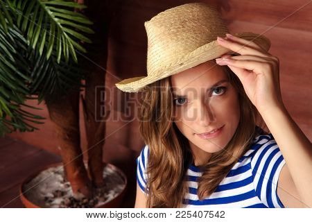 Beautiful Woman In A Striped Shirt Holding Her Straw Hat And Looking At A Camera. Wooden Veranda Of