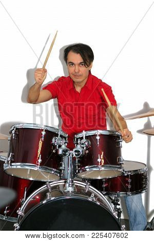 Middle Aged Drummer In Red Shirt With Drumsticks In His Hands Playing Drum Set. Isolated On A White