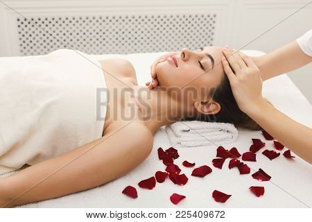 Facial Massage. Spa, Resort, Beauty And Health Concept. Beautiful Woman Getting Professional Face Tr