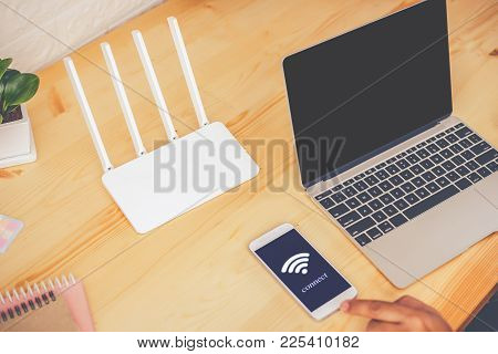 Young Man Using Mobile With Connect Wifi On The Screen. Man's Hands Using Device At Home Office. Blu