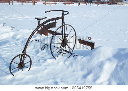Iron Sculpture Of Bicycle In White Snow On Winter Time