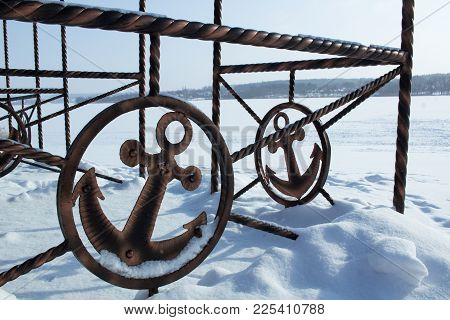 Iron Sign Of Ancor On Winter Coast Covered With Snow