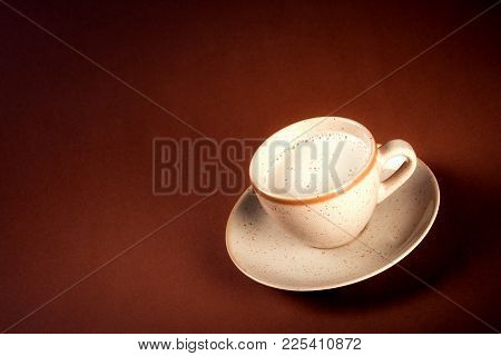 The Beige Cup Of Coffee With Frothy Milk Is On Dark Brown Background.