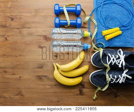 Fitness Concept With Sneakers Dumbbells Skipping Rope Measure Tape Towel Bottle Of Water And Bananas