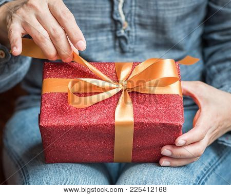 Boxing Day, Happy New Year & Merry Christmas Concept With Woman Opening Gift Box Untie Ribbon On Hol