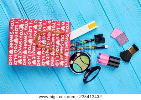 Red Shopping Bag And Cosmetics. Makeup Bag With Cosmetic Beauty Products Spilling Out On To Blue Woo