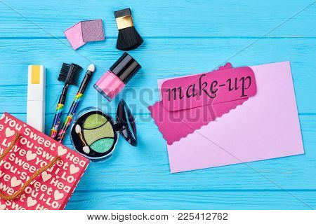 Beautiful Make Up Cosmetics Composition. Gift Bag And Cosmetics, Blue Wooden Background. Pink Card W