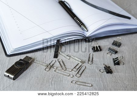 Open Notepad And Scattered Stationery: A Pen, A Pencil, Paper Clips, Binder Clips, A Pencil Sharpene