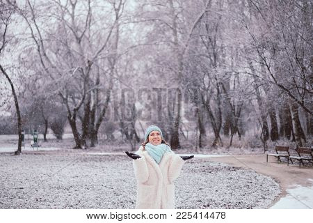 Smiling Young Woman In Snowing Outdoor At Park