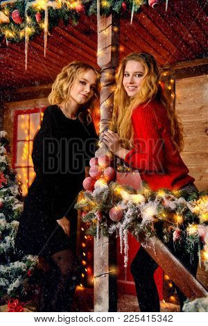 Beautiful young women a standing on the porch of a house decorated for Christmas. Time for miracles. Merry Christmas and Happy New Year.