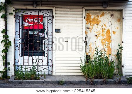 Warsaw, Poland - July 16, 2014: Coca Cola Red Weathered Sign On A White Siding Wall. Rusty Door Bars