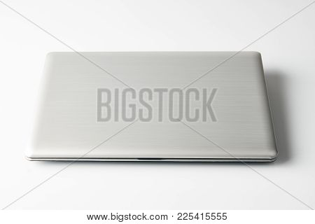 Closed Laptop Isolated On White Background, Close-up. Modern Silver Gray Laptop In The Closed Positi
