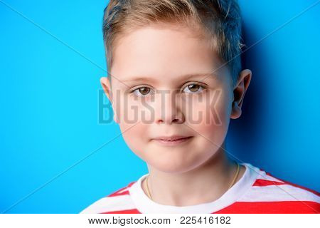 Portrait of a cute boy over bright blue background. Clothes for children. Kid's fashion.