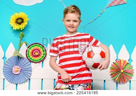 Portrait of a boy with a ball in summer decorations. Healthy lifestyle. Sports and activities for children. Football.