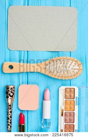 Makeup Items On Blue Wooden Background. Decorative Cosmetics And Natural Hair Brush, Top View. Empty