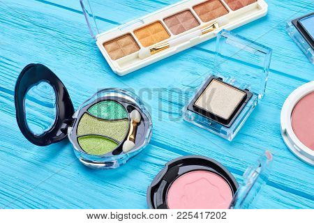 Set Of Color Eyeshadows On Blue Background. Compact Multicolored Eyeshadows On Wooden Table. Woman B
