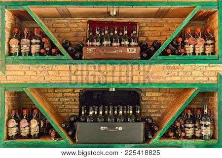 Batumi Georgia 11 July 2017: Many Wine Bottles On Wooden Shelves On A Brick Wall In Old Suitcases .