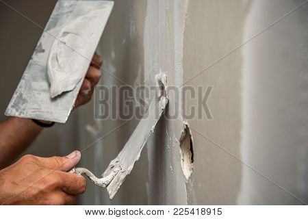 Old Manual Worker With Wall Plastering Tools Renovating House. Plasterer Renovating Indoor Walls And