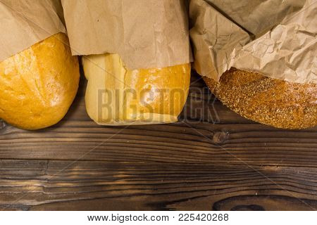 Assortment Of Bread Packed In Paper On Wooden Table. Top View, Copy Space