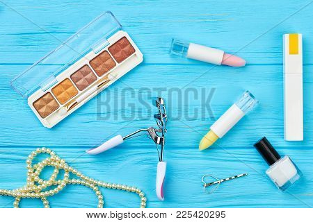 Cosmetics For Make-up, Top View. Flat Lay Lipstick, Eyeshadow, Nail Polish, Eyelashes Curler And Bea