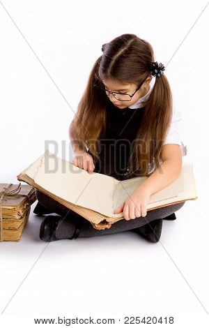 A Little Schoolgirl In Glasses Holds An Enormous Old Book In Her Hands And Reads It Sitting On The F