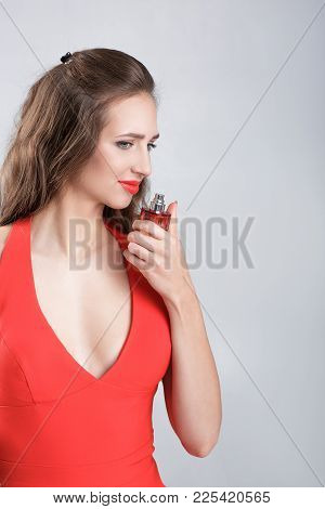 Young Woman In Red Dress Smelling Perfume. Unpleasant Smell