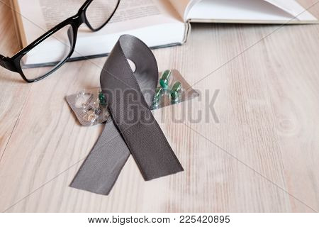 On A Wooden Table Lies A Gray Ribbon Of Awareness Of Parkinsons Disease. As A Symbol Of Parkinsons D