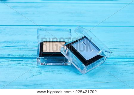 Blue And Beige Eyeshadows, Blue Background. Fashion Color Eyeshadows In Compact Box, Wooden Backgrou