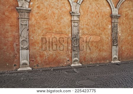 Old Wall With Scratched Stained Plaster, Ancient Stone Columns And Porphyry Sidewalk - Orange Pastel