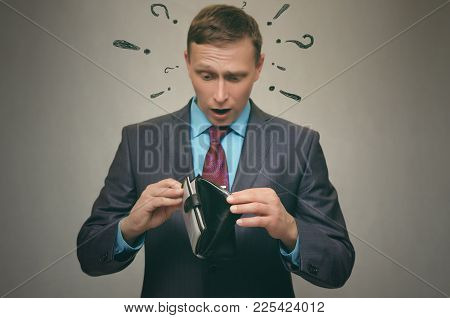 Business man is looking for money in his wallet. Pay the debt. Bankruptcy concept. A little salary. poster