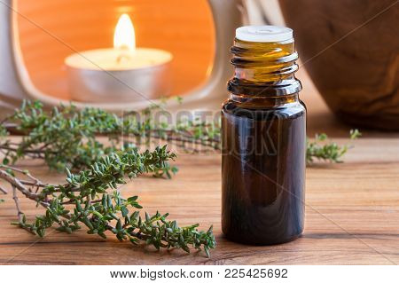 A Dark Bottle Of Thyme Essential Oil With Fresh Thyme Twigs And An Aroma Lamp In The Background