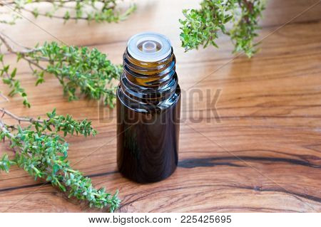 A Dark Bottle Of Thyme Essential Oil With Fresh Thyme Twigs In The Background, With Copy Space