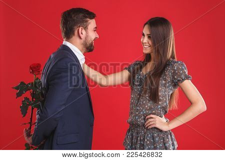 Love, Romance, Valentines Day, Couple And People Concept - Happy Young Man Giving Red Flower To Smil