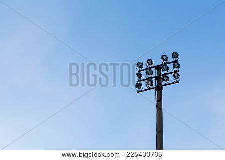 Lighting Mast With Searchlights On The Blue Sky Background