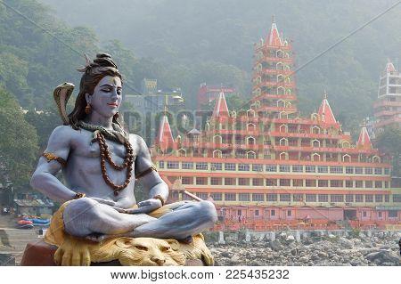 Rishikesh, India - November, 3rd, 2017. Statue Of Shiva Sitting In Meditation On The Riverbank Of Ga