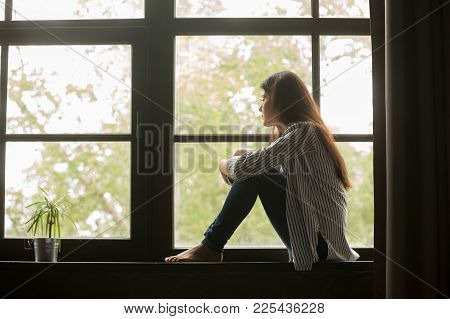 Thoughtful Girl Sitting On Sill Embracing Knees Looking At Window, Sad Depressed Teenager Spending T