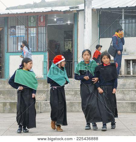 Tungurahua, Ecuador - Dec 20, 2017: Young Ecuadorian Indigenous Schoolgirls Post For A Picture Outsi