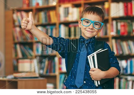 Smiling Boy With Blue Glasses Frame, Tie, Backpack And A Stack Of Books Showing The Cool Sign With H