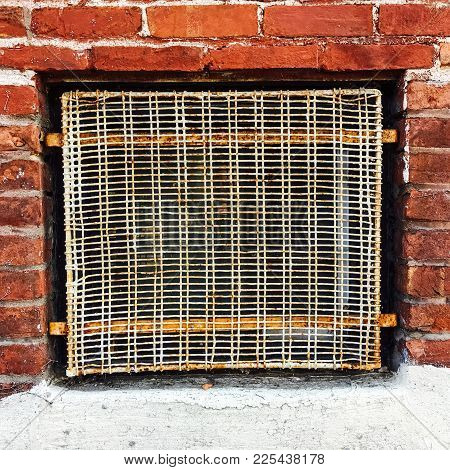 Old Wire Mesh Protecting Basement Window Of A Red Brick Building.