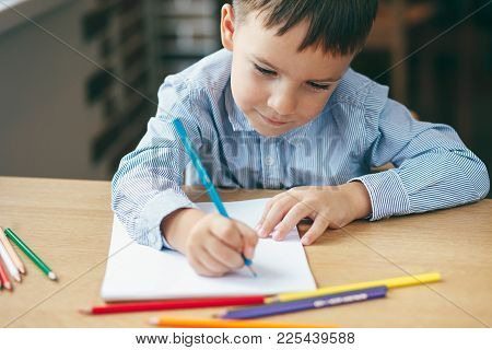 Close-up, Cute  Boy Doing Homework,  Coloring Pages, Writing And Painting. Children Paint. Kids Draw
