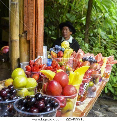 Banos, Ecuador - December 24th, 2017: Local Tropical Fruits For Sale With Indigenous Ecuadorian Man