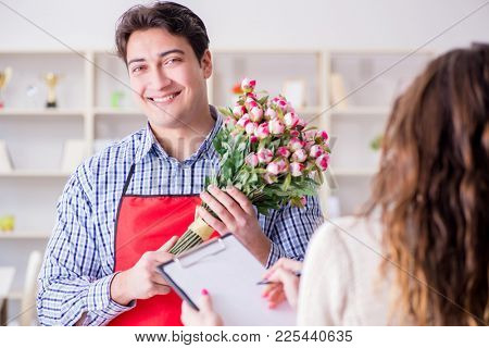 Flower shop assistant selling flowers to female customer